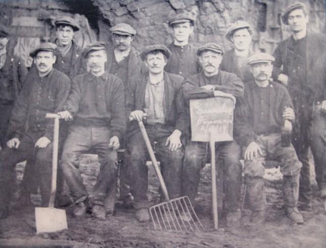 Eleven men outside a furnace at Summerlee Ironworks in 1919